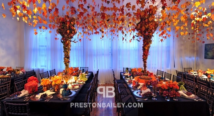 candles centerpiece dining entertaining holiday inspirations indoor leaves long table table setting tall centerpiece thanksgiving color|brown color|orange color|red